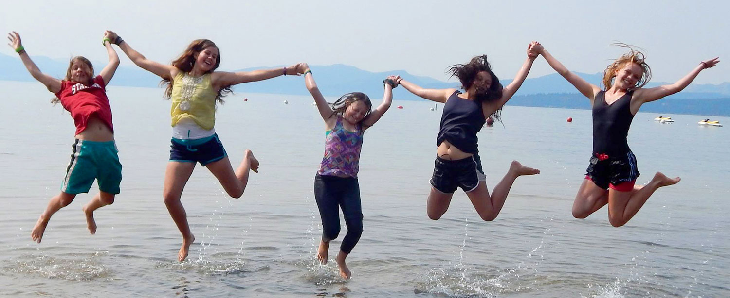 students jumping in ocean