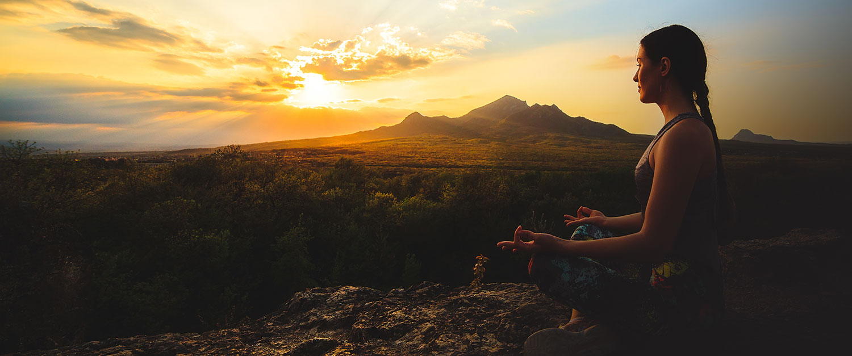 student meditating at sunset